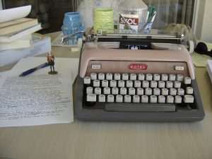 A brown Royal typewriters, a typed manuscript, and a bottle of Skol vodka. One of these things will be at the Kerouac House write-in. (Hint: Not the vodka.)